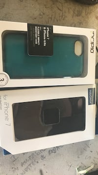 Two black and green phone cases in box