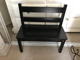 Black wooden bench made for two toddlers to sit on