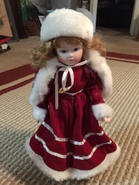 Red and white porcelain doll on stand.