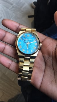 round blue analog watch with gold link bracelet