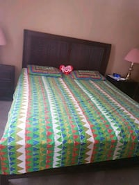 brown wooden bed with green and multicolored bedding set London, N6G 4E9