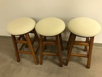 STOOLS...Three brown wooden base and cream padded stools Manassas, 20110