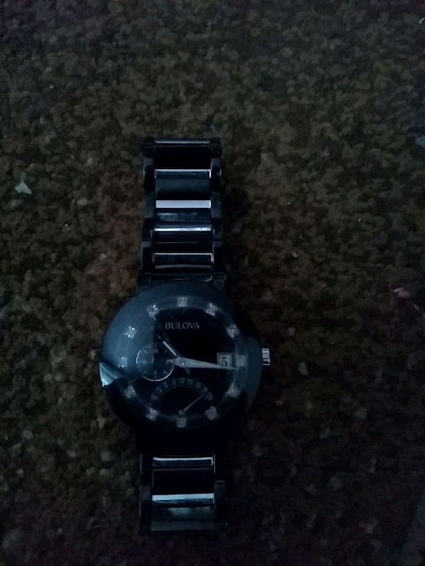 round black chronograph watch with link bracelet