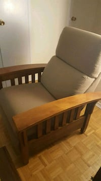 Brown wooden framed gray padded armchair.