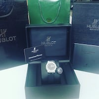 round silver-colored Hublot analog watch with black strap and box