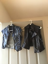 two black and blue leather and denim vests