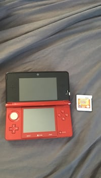 Red and black Nintendo 3DS with Pokemon Sun