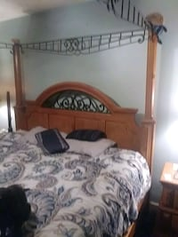 brown wooden bed frame and white mattress