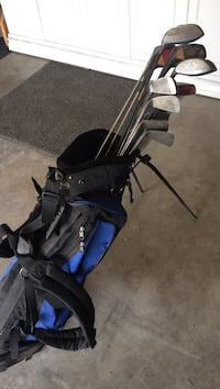gray golf club lot and black and blue bag