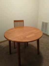 round brown wooden table with black metal base Des Moines, 50310