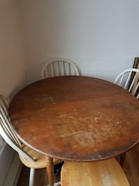 round brown wooden table with four windsor chairs