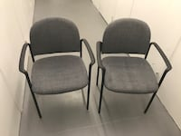 two black framed grey padded armchairs