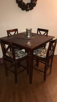 Square brown wooden table with four chairs dining set