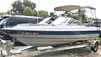 white and blue motorized boat with boat trailer