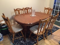 Oval brown wooden dining table with six chairs set Sterling