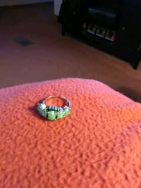 silver-colored ring with green gemstones