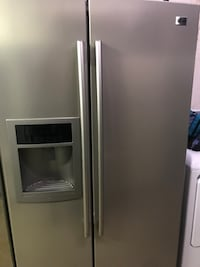 """Stainless steel """"LG""""side-by-side refrigerator with dispenser"""