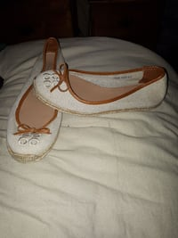 pair of women's white and brown Coach flats
