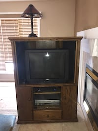 Black crt tv with brown wooden tv hutch