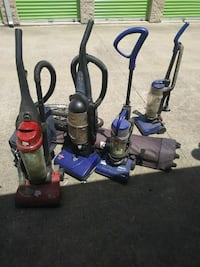 two black and blue upright vacuum cleaners