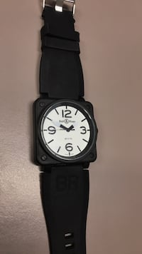 Round black analog watch with black strap