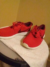 pair of red Nike running shoes 550 km