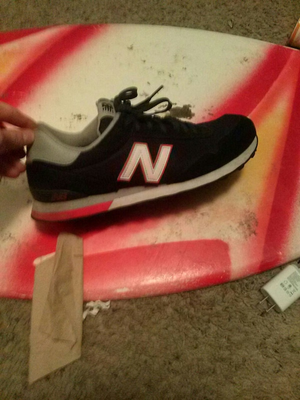 black, white, and red New Balance 574 sneaker