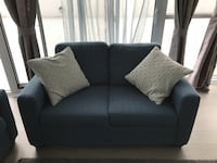 Blue velvet fabric loveseat with throw pillows