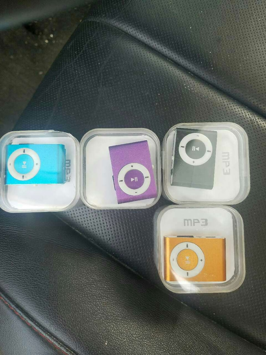 four blue, black, and pink MP3 players in cases