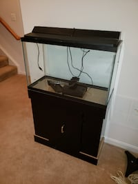 25 gallon fish tank with cabinet stand, light and  32 km