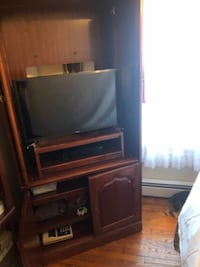 brown wooden TV hutch with flat screen television NEWYORK