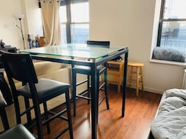 Dining table with glass top and four high chairs
