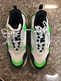 pair of white-and-green Nike running shoes null