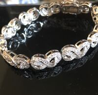 silver-colored infinity link bracelet with clear gemstones