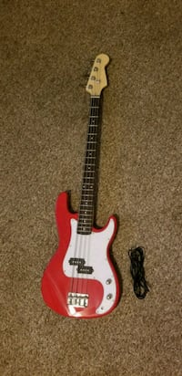 red and white electric bass guitar with cord