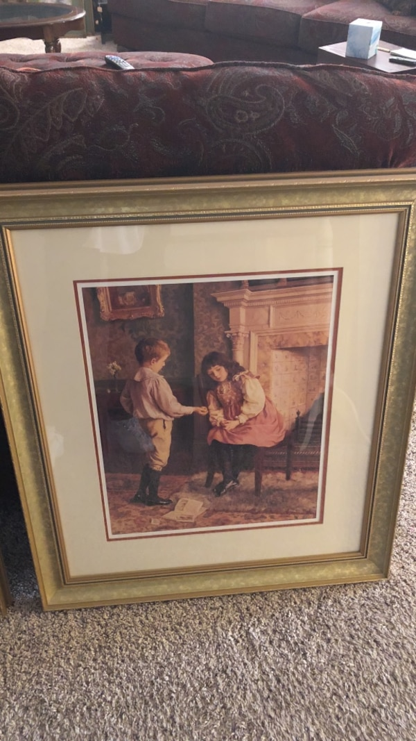 brown wooden framed painting of girl and boy sitting on brown chair
