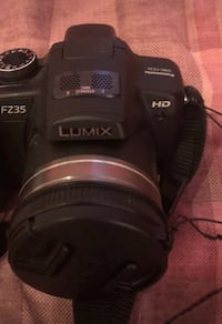 Black panasonic Lumix camera with bag and manual