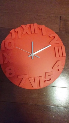 round orange and stainless steel analog wall clock