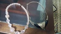 two clear white and gold-colored necklaces