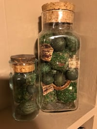 two clear glass bottles with green ball decors