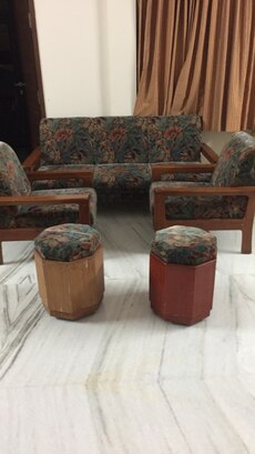 brown teak wood sofa set with white and pink floral pads