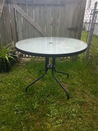 round glass-top table with black steel frame London, N5W