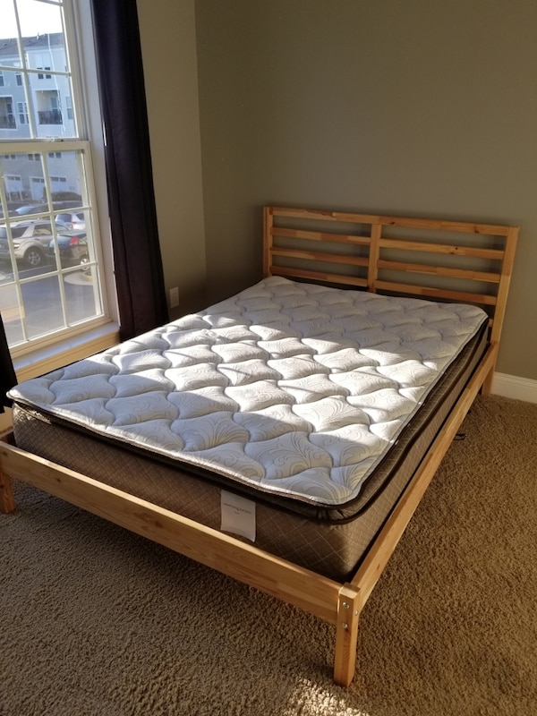 Brown wooden bed frame with white mattress ikea d1032f08-f641-4d12-9fe4-f6233e3bd541