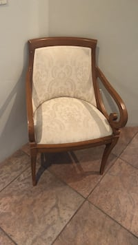 Brown wooden framed white floral padded armchair
