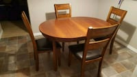 round brown wooden table with four chairs dining s Edmonton, T6M 0M3