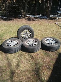 four gray 5-spoke car wheels with tires