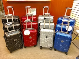 Four assorted color hard shell luggage