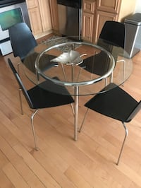 Round Glass Silver Table with four black chair silver legs Washington