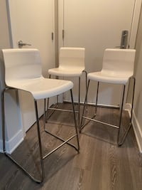 3 white barstools together