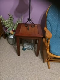 brown wooden side table and two white ceramic vase 417 mi